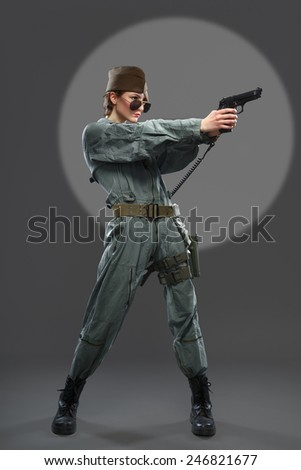 A girl dressed as a helicopter pilot with a gun in his hand