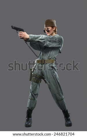 A girl dressed as a helicopter pilot with a gun in his hand isolated on grey background