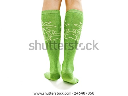 A girl dressing green-white socks from the back. Isolated on white background  - stock photo
