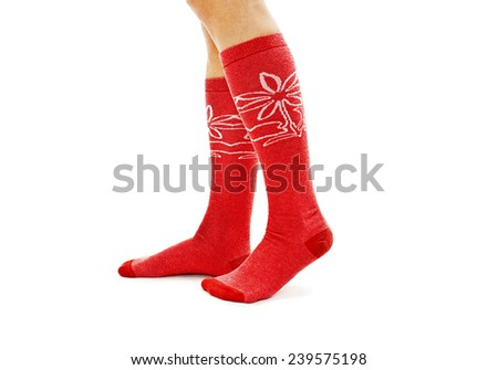A girl dressing red-white socks. Isolated on white background  - stock photo
