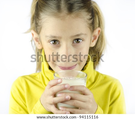 A girl drinking cow's milk in a glass.