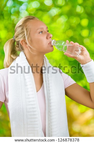 a girl drinking water fom small bottle