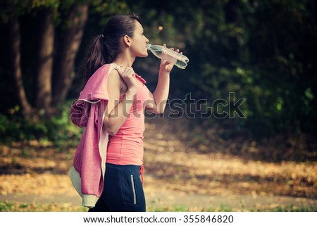 a girl drinks water after sport - stock photo