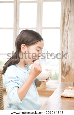 A girl eating white rice