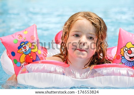 A girl floating on an inflatable toy in the water. - stock photo