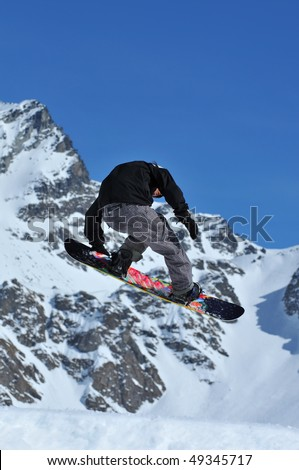 a girl freestyle snowboarder performing a jump and touching her board