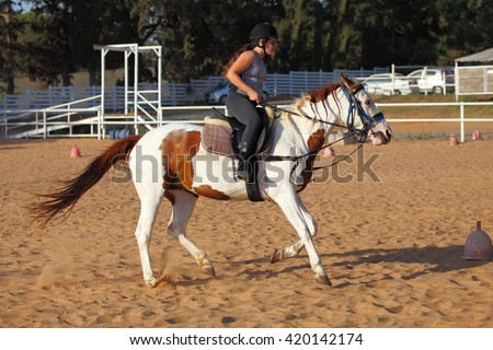 A girl getting a horseback riding lesson  - stock photo