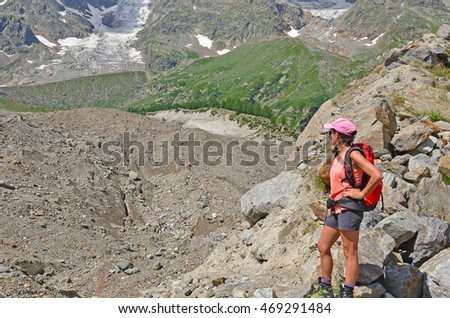 A girl hiker looks out over a moraine covered glacier in the mountains