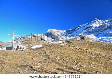 A girl hiker sits by a mountain hut on a high pass with a cross on a beautiful clear day. Rawil pass with the Weisshorn in the background in the Swiss Alps - stock photo