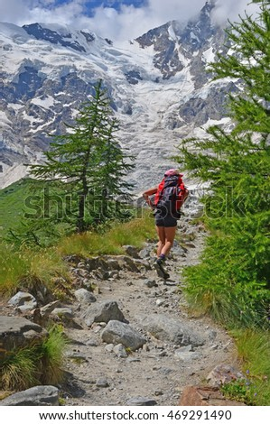 A girl hiker walks up a steep path in the mountains towards glaciers and steep peaks