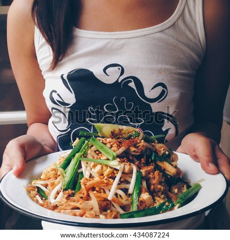 A girl hold and offer a dish of healthy authentic Padthai (an original Thai style stir fried noodle with mixed herb, spice and tamarind sauce) with grilled Tofu,crushed grilled peanut and lemon wage. - stock photo