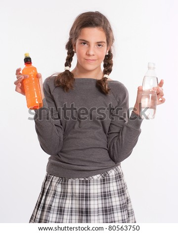 A girl holding a bottle in each hand, one with water, the other a bright orange beverage