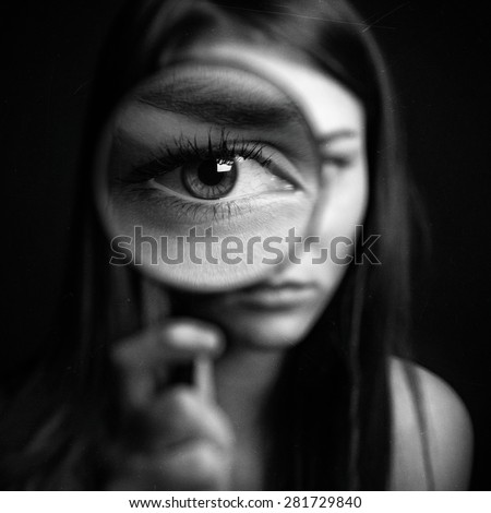 A girl holding a magnifying glass on a dark background, scary big eyes - stock photo