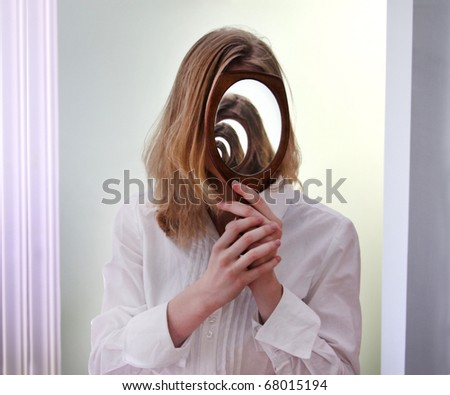 A girl holding a mirror over her face in front of a larger mirror, creating the illusion of infinite reflections. - stock photo