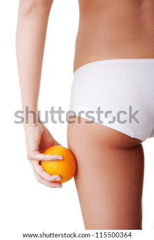 A girl holding an orange next to the buttocks is isolated on white - stock photo