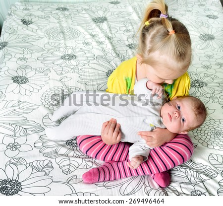 A girl holding in her arms her younger three month old sister sitting cross-legged on a bed. - stock photo