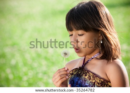 a girl holds a dandelion weed and blows it in a field - stock photo