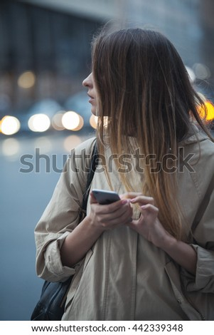 a girl holds a phone and looks to the side, standing on the street in the evening