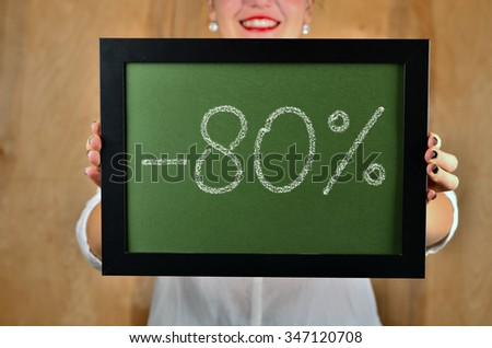 a girl holds a sign saying sale - 80 percent - stock photo