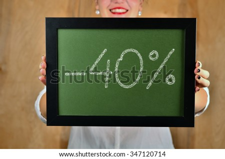 a girl holds a sign saying sale - 40 percent - stock photo