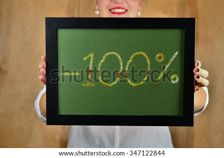 a girl holds a sign saying sale - 100 percent - stock photo