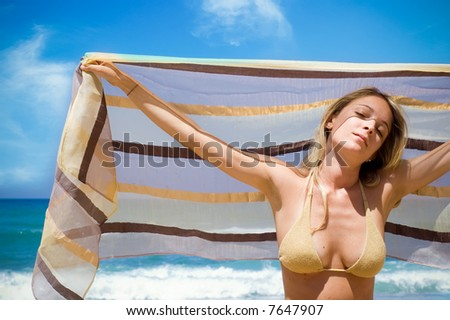 a girl holds a silken fabric over the head. Beach scenic.