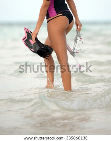 a girl in a bikini walking on the beach with snorkel gear and fins - stock photo