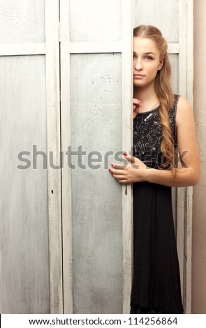 A girl in a black dress peeks out from behind the closet door studio photography - stock photo