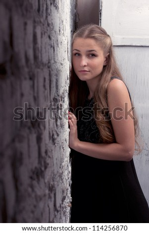 A girl in a black dress with long flowing hair leaning body to a brick wall - stock photo