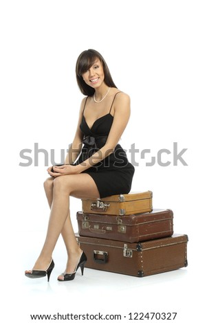 A girl in a black short dress sitting on suitcases