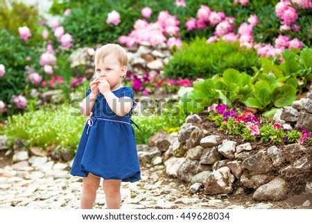 A girl in a blue polka-dot dress walks in the Park with flowerbeds - stock photo