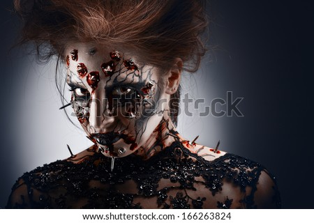 A girl in a creepy halloween costume of a witch with peircing and cracked face paint looking with disguise. - stock photo