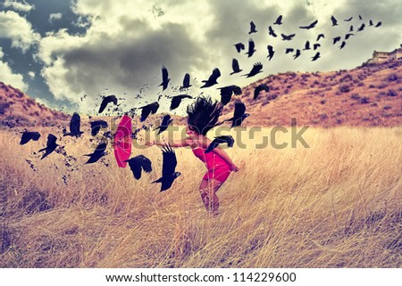 a girl in a field with an umbrella pointing toward a flock of birds - stock photo