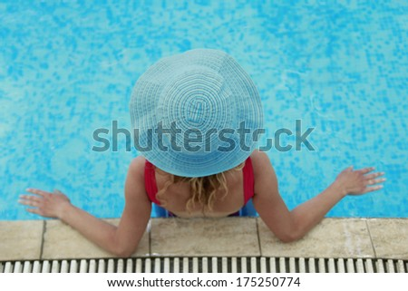 a girl in a hat in the water pool