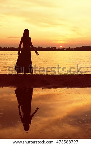 A girl in a long dress stands on a sand spit reflected in the waters of the river and looking at the setting sun on the horizon