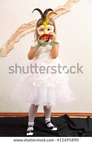 a girl in a mask and white dress - stock photo