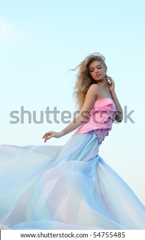 A girl in a skirt billowing against the sky - stock photo