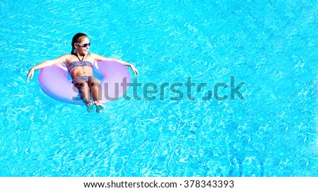 A girl in a swimsuit in the pool on an inflatable circle summer