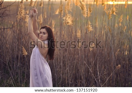 A girl in a white cloth on a background of dry reeds - stock photo