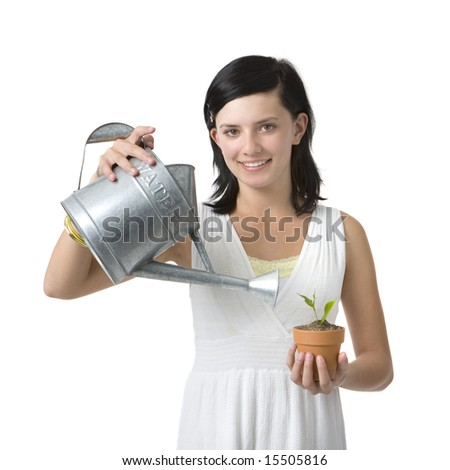 A girl in a white dress waters a plant in her hand
