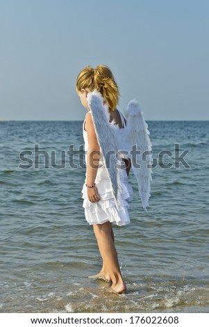 A girl in a white dress with wings, walking in the water.