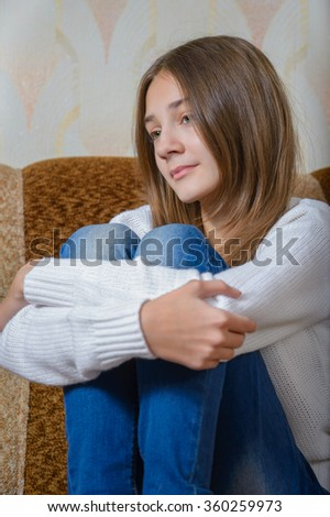 A girl in a white sweater and jeans sitting on the couch and dreams