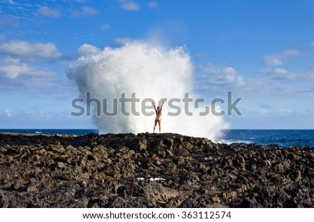 A girl in bikini enjoys the waves crashing into the volcanic rocks on the westcoast of Reunion Island in the Indian Ocean - stock photo