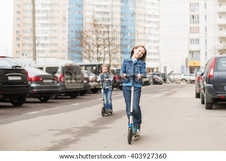 A girl in jeans suit riding a scooter on road parking. - stock photo