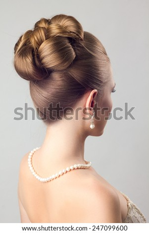 A girl in pearl necklace with wedding hairstyle, view from the back - stock photo
