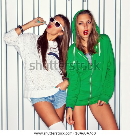 a girl in stockings is sucking a red lollipop while the other in sexy shorts is looking in the camera   - stock photo