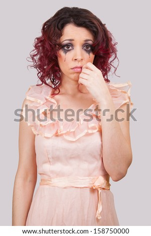 A girl in tears. Facial emotions of a young woman in vintage dress - stock photo