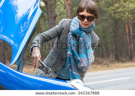 A girl is at a loss with the wrong wrench over the open car hood in the forest. - stock photo