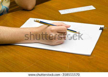 A girl is drawing a rose on a pile of paper for Valentine's event