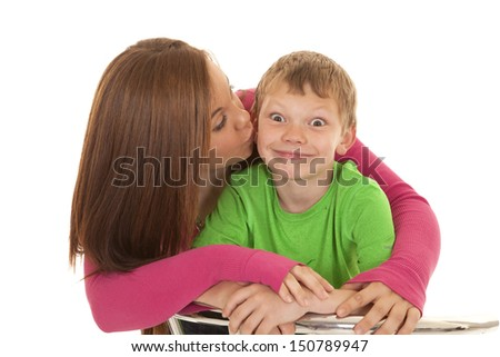 A girl is kissing a young boy on the cheek.